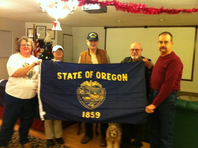 Rep. Greg Smith (via aid Phil Scheuers) presents State flag flown over State Capital